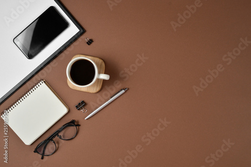 Fototapeta Creative flat lay, top view office table desk. Workspace with blank clip board, office supplies, pen, notepad, smartphone, glasses and coffee cup on a brown background. obraz na płótnie