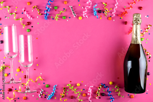 Fényképezés  Bottle of champagne, flute glasses with confetti, streamers and other party attributes in flat lay composition on bright paper background