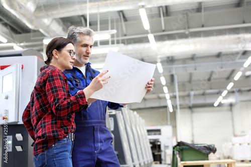 Obraz Drukarnia. Kobieta i mężczyzna oglądają wydruk - fototapety do salonu