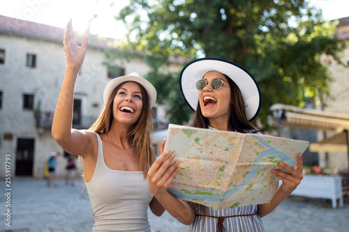 Fototapeta Young happy tourists women sightseeing in city on vacation obraz