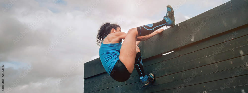 Fototapeta Participant in obstacle course climbing wall