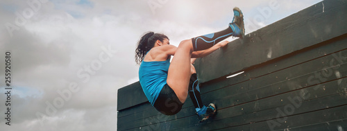 Participant in obstacle course climbing wall Wallpaper Mural