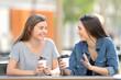Leinwanddruck Bild - Two friends talking and drinking in a park