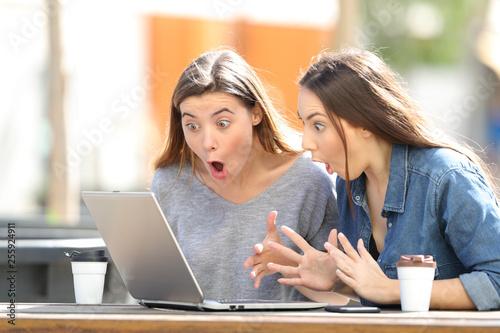 Fotografija  Amazed friends finding online content on laptop in a park