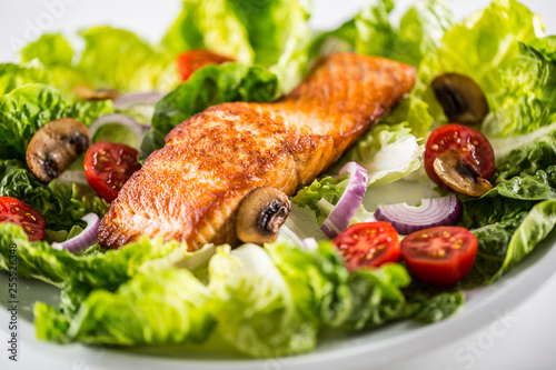 Roasted salmon fillet with fresh vegetable salad on white plate Fototapete