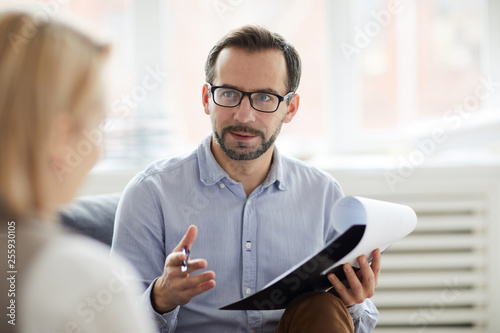 Young confident counselor with pen and document explaining something to his patient during conversation
