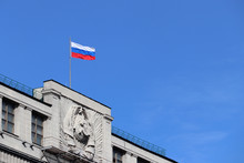 Russian Flag On The Parliament Building In Moscow Against Blue Sky. Facade Of State Duma Of Russia With Soviet Coat Of Arms, Russian Authority