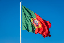Portuguese Flag Against Blue Sky In Eduardo VII Park In Lisbon City, Portugal