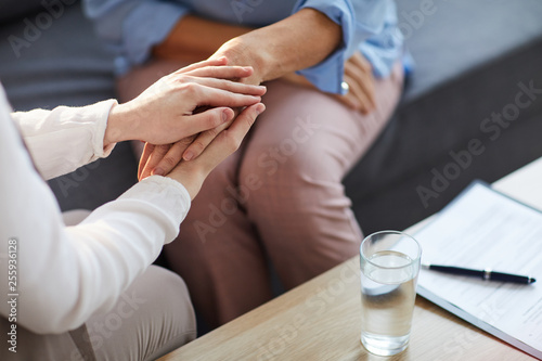 Fotomural Young psychologist holding hand of her patient in need while consulting her afte