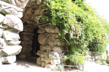 An Artificial Cave Made Of Rocks And Covered With Plants