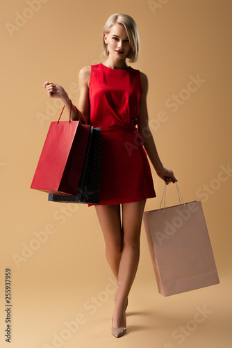 Obraz Full length view of beautiful young woman in red dress holding shopping bags - fototapety do salonu