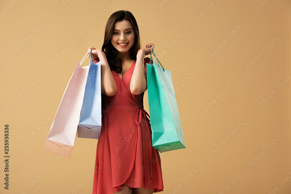 Fototapeta smiling and beautiful young woman in red dress holding shopping bags isolated on beige