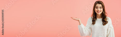 panoramic shot of beautiful woman in white sweater pointing with hand isolated on pink