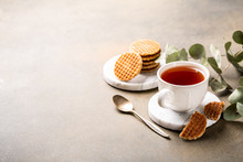 Cup Of Tea With Mini Stroopwafel, Syrupwaffles Cookies And Eucalyptus Twigs On Light Background With Copy Space.