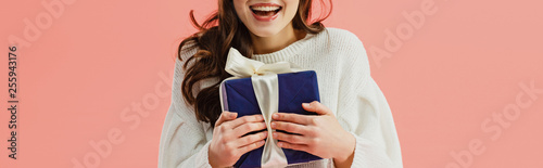 cropped view of woman in white sweater holding gift box isolated on pink Fototapete