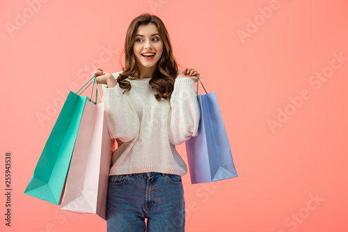 Fototapeta smiling and attractive woman in white sweater holding shopping bags isolated on pink obraz