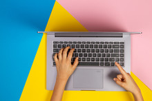 Kid Hands Typing On Laptop Computer Keyboard On Multicolored Background, Top View