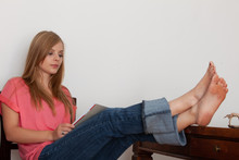 Attractive Young Woman Relaxing At Home With Her Bare Feet Up On The Table
