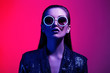 canvas print picture - Fashion girl with long hair and round sunglasses in a black shining dress poses in neon light in the studio
