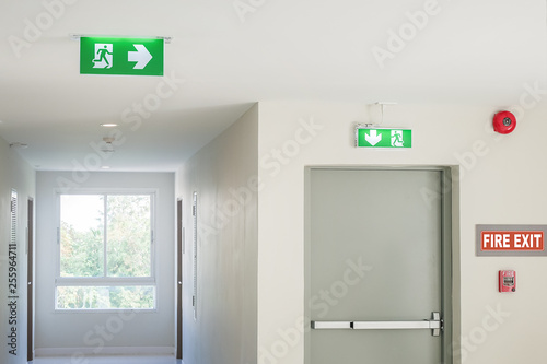 Fire exit sign with light on the path way in the hotel or office Fototapeta