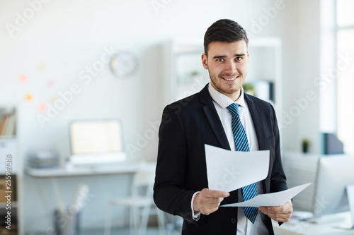фотографія Smiling young successful banker in elegant suit looking through financial docume