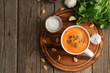 Pupmkin cream soup in cup on brown wooden table, top view, copy space. Dietary vegetarian puree on cutting board with parsley, garlic.