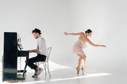 Fototapeta beautiful ballerina in pink dress dancing while handsome pianist playing piano