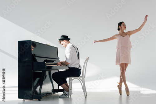 Foto musician playing piano and dancing graceful ballerina