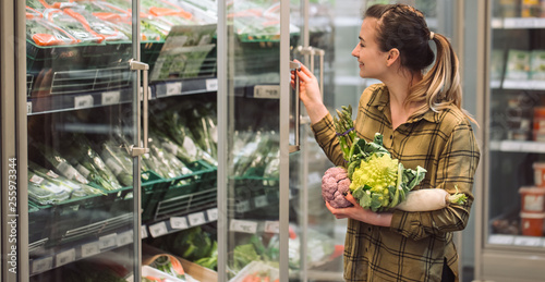 Woman in the supermarket. Beautiful young woman holds in hands fresh organic vegetables and opens the fridge in the supermarket