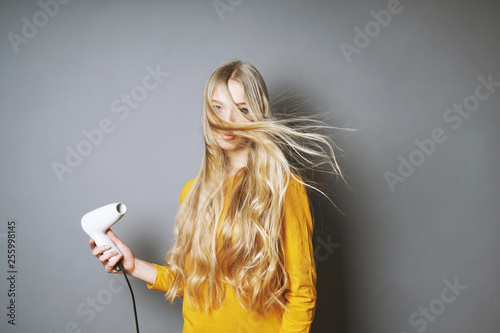 Photo funny young blond woman blow-drying her long hair with blow dryer