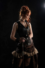 A Beautiful Red-haired Cosplayer Girl Wearing A Victorian-style Steampunk Costume With A Big Breast In A Deep Neckline Stands Thoughtfully, Leaning On A Cane, On A Dark Background.
