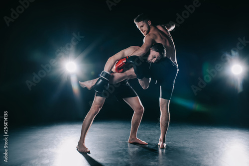 barefoot strong muscular mma fighter in boxing gloves clinching another while sp Canvas-taulu