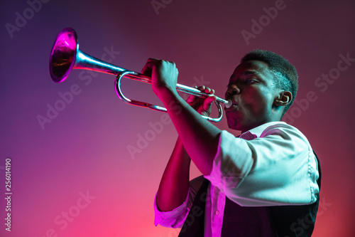 African American handsome jazz musician playing trumpet in the studio on a neon background. Music concept. Young joyful attractive guy improvising. Close-up retro portrait. - 256014190