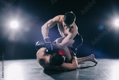 Obrazy MMA   shirtless-muscular-strong-mma-fighter-in-boxing-gloves-clinching-opponent-on-floor