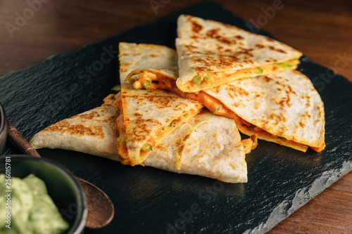 Close up Baked Chicken and Cheese Quesadillas served with Salsa and Guacamole on stone plate Wallpaper Mural