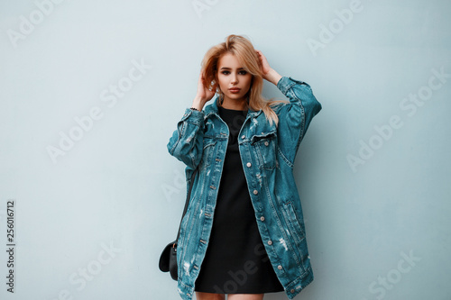 Cuadros en Lienzo American glamorous young blonde with a fashionable blue denim jacket in a stylish black dress with a leather handbag posing in a room near a vintage wall