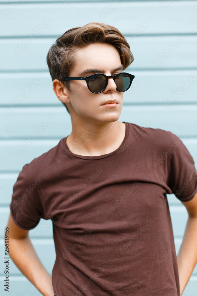 Fototapeta Handsome young fashionable hipster man in stylish sunglasses in brown t-shirt poses in the city near the blue wooden building on a summer day. Attractive modern trendy teenage guy.