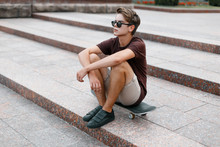 Young Handsome Hipster Man In Stylish Sunglasses In Stylish T-shirt In Trendy Shorts In Sneakers Resting On A Skateboard In The City On A Summer Day. American Modern Guy On Vacation.