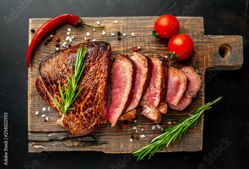 Beef steak, herbs and spices on a cutting board against a background of stone