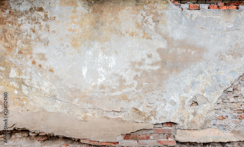 Wall Murals Old dirty textured wall Old grungy red brick wall with peeled beige stucco background. Vintage retro plaster wall with dirty cracked scratched texture background