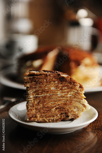 Valokuva  Piece of crepe cake with tiramisu filling and powdery cocoa is served on plate