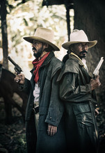 Close Up Two Cowboys Standing And Holding Handgun