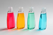 Three plastic bottles with liquid yellow, green and red soap.