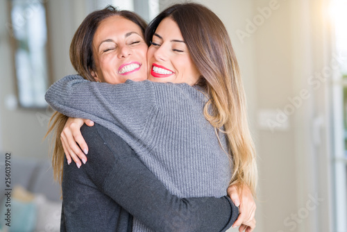 Obraz na płótnie Beautiful family of mother and daughter together, hugging and kissing at home