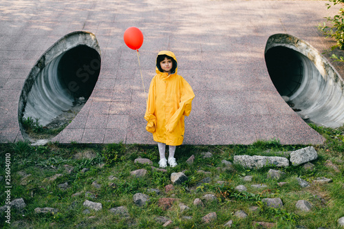 Photo  Portrait of pretty litle girl in big adult oversized yellow raincoat with red balloon in hand standing and sitting against sewage tunnel pipe