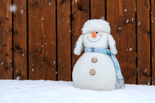 Funny Plush Snowman In Front Of A Wooden Wall During Snowfall