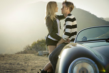 Young Couple Embrace Against Convertible