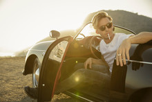 Stylish Young Man Holds Unlit Cigarette In Convertible