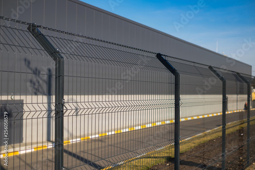 Fotografia Steel grating fence made with wire on blue sky background