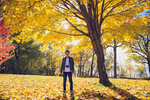 Teenage Boy With Camera Standing Under Tree With Fall Foilage In Park